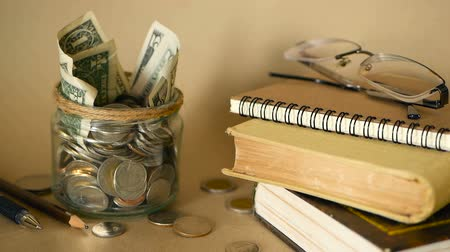 mevduat : Books with glass penny jar filled with coins and banknotes. Tuition or education financing concept. Scholarship money. Savings for future education. Books, glasses, clock in background. Soft focus