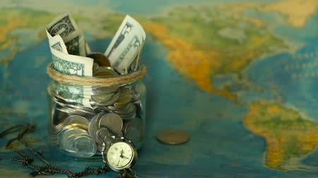 монета : Travel budget concept. Money saved for vacation in glass jar on world map background, copy space. Banknotes and coins for adventure. Savings for journey. Collecting money for trip. Moneybox with cash.