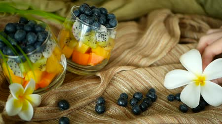 papája : Colorful tropical mix salad in jar. Fresh various kind of raw organic berry and fruit in glass bowl. Healthy vegetarian eating, balanced, vegan diet. Rustic food background with falling blueberrys