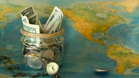 экономить : Travel budget concept. Money saved for vacation in glass jar on world map background, copy space. Banknotes and coins for adventure. Savings for journey. Collecting money for trip. Moneybox with cash.