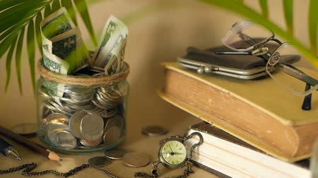 kumbara : Books with glass penny jar filled with coins and banknotes. Tuition or education financing concept. Scholarship money. Savings for future education. Books, glasses, clock in background. Soft focus