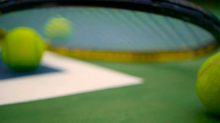 esportivo : Close up of tennis equipment on the court. Sport, recreation concept. Yellow racket with a tennis ball in motion on a clay green blue court next to the white line with copy space and soft focus. Stock Footage