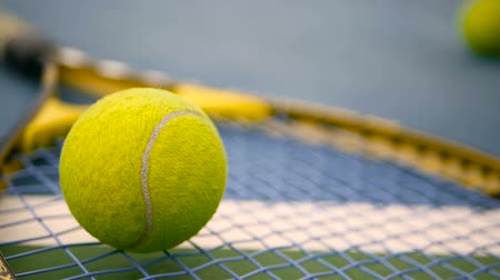 лидер : Close up of tennis equipment on the court. Sport, recreation concept. Yellow racket with a tennis ball in motion on a clay green blue court next to the white line with copy space and soft focus. Стоковые видеозаписи
