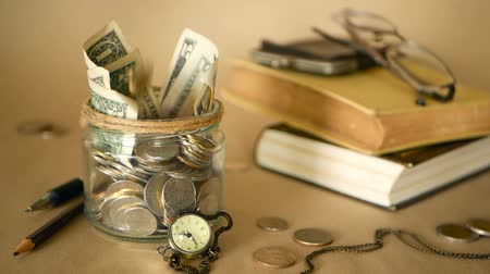 monety : Books with glass penny jar filled with coins and banknotes. Tuition or education financing concept. Scholarship money. Savings for future education. Books, glasses, clock in background. Soft focus