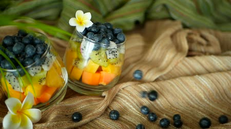 manga : Colorful tropical mix salad in jar. Fresh various kind of raw organic berry and fruit in glass bowl. Healthy vegetarian eating, balanced, vegan diet. Rustic food background with falling blueberrys