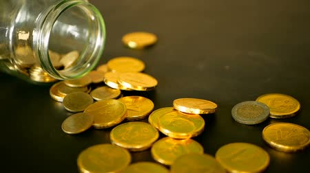 para kazanmak : Yellow coins fell out from jar. Symbol of investing, keeping money concept. Collecting cash conis in glass tin as moneybox. Close-up still life with gold coins on black table and rotating penny. Stok Video