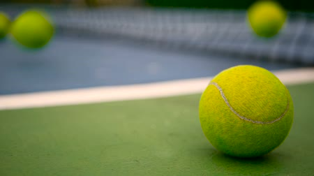 glinka : Close up of tennis equipment on the court. Sport, recreation concept. Yellow tennis balls in motion on a clay green blue court next to the white line with copy space, soft focus and net in background.