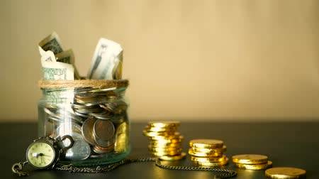 currency trading : Saving money coin in jar. Symbol of investing, keeping money concept. Collecting cash banknotes in glass tin. American dollars with increasing columns of gold coins on black table with retro clock.