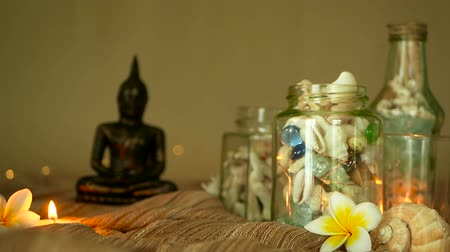 flowers background : Glass jar of tropical shells for home decor. Marine style, beach themed interior decorating. Bottle filled with seashells, corals, marine items with candle lights, plumeria flowers and sitting buddha Stock Footage