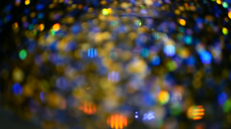 fényesen : Defocused shimmering multicolored glitter confetti, black background. Party, magic, imagination. Rainbow colors, sparkle circles. Holiday abstract festive texture of shiny blurred bokeh light spots. Stock mozgókép