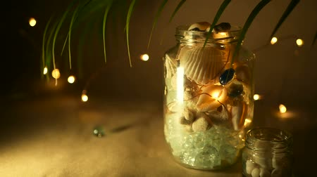 sznurek : Glass jar of tropical shells for home decor. Marine style home accessories for beach themed interior decorating. Bottle filled with seashells, corals, marine items with lights in unfocused background.