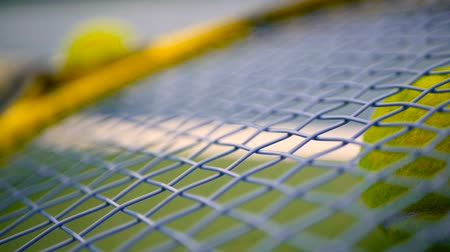 racchetta tennis : Close up of tennis equipment on the court. Sport, recreation concept. Yellow racket with a tennis ball in motion on a clay green blue court next to the white line with copy space and soft focus. Filmati Stock