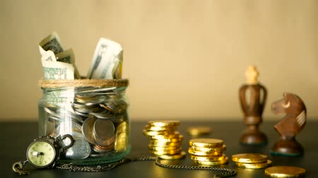 oran : Saving money coin in jar. Symbol of investing, keeping money concept. Collecting cash banknotes in glass tin. American dollars with increasing columns of gold coins on black with retro clock, chess.