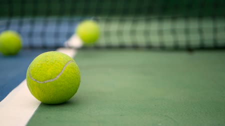 ракетка : Close up of tennis equipment on the court. Sport, recreation concept. Yellow tennis balls in motion on a clay green blue court next to the white line with copy space, soft focus and net in background.