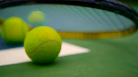 ракетка : Close up of tennis equipment on the court. Sport, recreation concept. Yellow racket with a tennis ball in motion on a clay green blue court next to the white line with copy space and soft focus. Стоковые видеозаписи