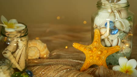 sznurek : Glass jar of tropical shells for home decor. Marine style, beach themed interior decorating. Bottle filled with seashells, corals, marine items, sea star with bokeh lights and plumeria flowers