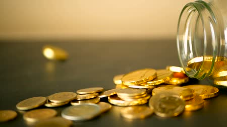 cent : Yellow coins fell out from jar. Symbol of investing, keeping money concept. Collecting cash conis in glass tin as moneybox. Close-up still life with gold coins on black table and rotating penny. Stock Footage