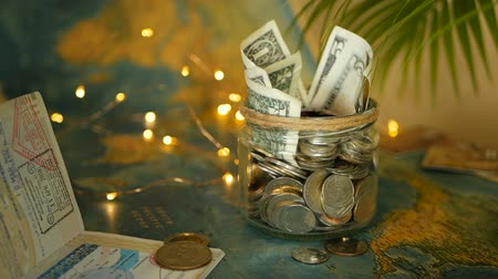 euro banknotes : Travel budget concept. Money saved for vacation in glass jar on world map background, copy space. Banknotes and coins for adventure. Savings for journey. Collecting money for trip. Moneybox with cash.