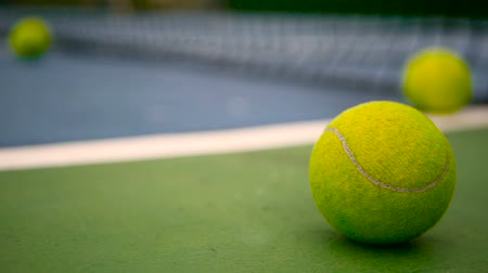 próximo : Close up of tennis equipment on the court. Sport, recreation concept. Yellow tennis balls in motion on a clay green blue court next to the white line with copy space, soft focus and net in background.