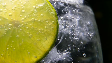 tonik : Macro close-up,refreshing soda tonic fizzy water, lime in Glass, ice. Slice of lemon, mineral bubbles. Detox or thirst concept. Healthy, dietary nutrition. Cold lemonade mojito drink. Black background