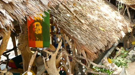 jamaica : Relaxing jamaican cannabis rasta marijuana reggae bar on the tropical summer beach from wooden branches and thatch. Rastafarian flags with yellow, red and green colors and bob marley. Stock Footage