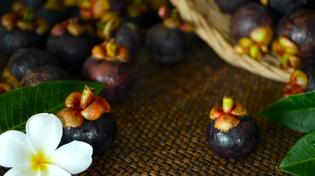 kraliçe : Top view of fresh delicious harvested mangosteens on wooden table. Thai organic purple fruit in the basket. Exotic natural blurred background with tropical flower. Healthy food and eating concept.