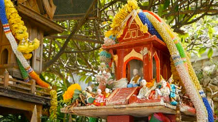 buddhizmus : Wooden miniature guardian spirit house. Small buddhist temple shrine, colorful flower garlands. San phra phum erected to bring fortune. Traditional respect animistic rituals, pray ceremonies Stock mozgókép