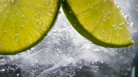 аперитив : Macro close-up,refreshing soda tonic fizzy water, lime in Glass, ice. Slice of lemon, mineral bubbles. Detox or thirst concept. Healthy, dietary nutrition. Cold lemonade mojito drink. Black background