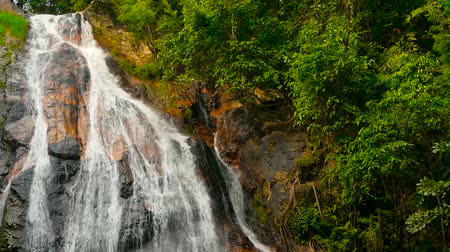 torrente : Jungle paradise landscape of tropical country. Waterfall cascade in green rain forest. Motion of water flow from cliff down. Exotic river and rocks. Natural seasonal travel outdoor background