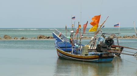 fishing village : Tropical ocean beach landscape with moored small wooden traditional colorful fishing boat. Seascape near asian poor Muslim fisherman village on Koh Samui island in Thailand. Flags and lamps aboard.