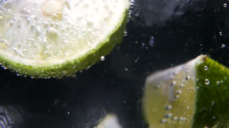 garnished : Macro close-up,refreshing soda tonic fizzy water, lime in Glass, ice. Slice of lemon, mineral bubbles. Detox or thirst concept. Healthy, dietary nutrition. Cold lemonade mojito drink. Black background