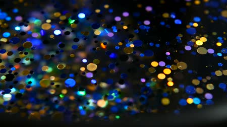 glittery : Defocused shimmering multicolored glitter confetti, black background. Party, magic, imagination. Rainbow colors, sparkle circles. Holiday abstract festive texture of shiny blurred bokeh light spots. Stock Footage