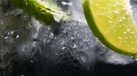 cytryna : Macro close-up,refreshing soda tonic fizzy water, lime in Glass, ice. Slice of lemon, mineral bubbles. Detox or thirst concept. Healthy, dietary nutrition. Cold lemonade mojito drink. Black background