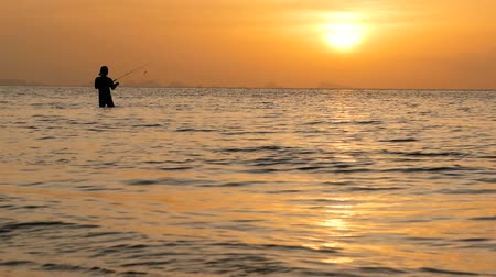 döküm : Fisherman silhouette in action when spinning on sunset time. Traditional Asian occupation and way of obtaining food.