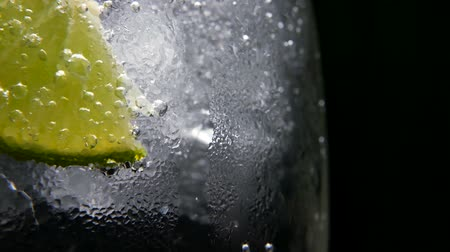 aperitief : Macro close-up, verfrissende soda tonic koolzuurhoudende water, kalk in glas, ijs. Plakje citroen, minerale bubbels. Detox of dorst concept. Gezonde voedingsvoeding. Koude limonademojitodrank. Zwarte achtergrond