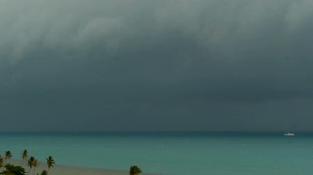 typhoon : Dramatic gloomy sky with dark thunderstorm clouds over turquoise sea. Hurricane on ocean horizon. Vivid aerial timelapse beautiful view of storm raining seascape. Tropical rain season, typhoon weather Stock Footage