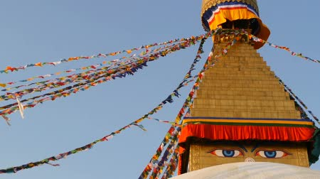 boudha : Colorful prayer flags flying in the wind at Boudhanath Stupa, Holy Pagoda, symbol of Nepal and Kathmandu with golgen Buddhas Eyes. Sunset ligth. Stock Footage