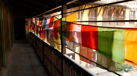 veranda : Colorful fabric pieces on house terrace. Perspective view of strings with colorful fabrics with prayers hanging above fence of terrace outdoors