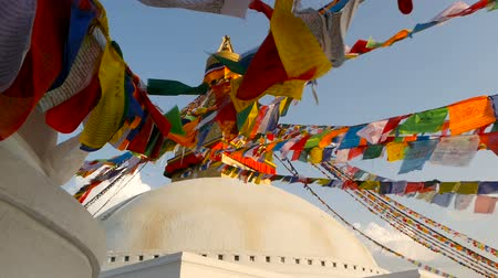 bodhnath : Colorful prayer flags flying in the wind at Boudhanath Stupa, Holy Pagoda, symbol of Nepal and Kathmandu with golgen Buddhas Eyes. Sunset ligth. Stock Footage