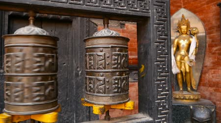 wheel of dharma : Row of aged religious prayer wheels or drums with mantra Om Mani Padme Hum in yard of temple, Durbar Square, Nepal, Kathmandu. Tibetian buddhism Stock Footage