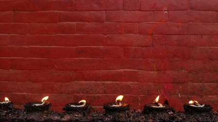 patan : Burning lamps against red brick wall. Row of burning memorial lamps on background of bright red wall of temple