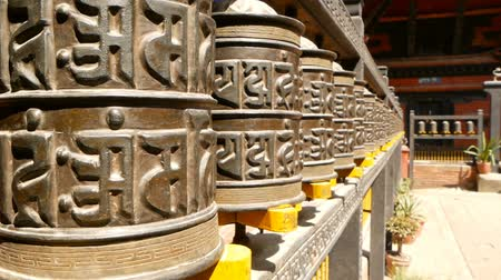 bodhnath : Row of aged religious prayer wheels or drums with mantra Om Mani Padme Hum in yard of temple, Durbar Square, Nepal, Kathmandu. Tibetian buddhism Stock Footage