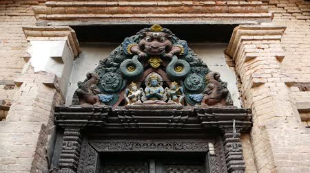 architectural heritage : Ornamental design, temple entrance. From below aged entrance with colorful wooden old sculpture of god above doorway. Kathmandu valley, Swayambhunath Stupa, Monkey Temple, Nepal. Shantipura Mahavihar Stock Footage
