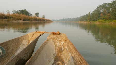 kano : Wooden boat swimming in river of national park. Beak of wooden boat floating in tranquil river of Chitwan national park, Nepal