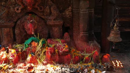 patan : Shrine with sculpture and candles burning. Hindu temple shrine outdoors with sculpture of Ganesha and burning candles in sunlight, Nepal