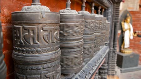patan : Row of aged religious prayer wheels or drums with mantra Om Mani Padme Hum in yard of temple, Durbar Square, Nepal, Kathmandu. Tibetian buddhism Stock Footage