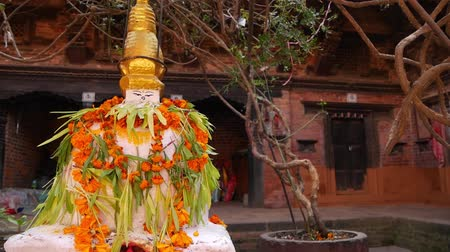 patan : Statue in yard of aged oriental temple. White statue with colorful garlands in stone yard of Buddhist temple, Nepal Stock Footage