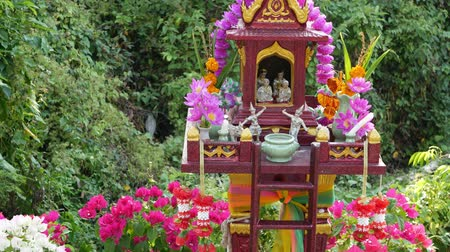 guardian : Wooden miniature guardian spirit house. Small buddhist temple shrine, colorful flower garlands. San phra phum erected to bring fortune. Traditional respect animistic rituals, pray ceremonies. Stock Footage