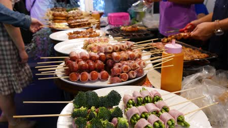 Traditional Asian night street food market in Thailand. Barbecue meatballs and other exotic delicious snacks for sail. Ready to eat food. Stock mozgókép