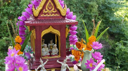 Wooden miniature guardian spirit house. Small buddhist temple shrine, colorful flower garlands. San phra phum erected to bring fortune. Traditional respect animistic rituals, pray ceremonies. Stock mozgókép